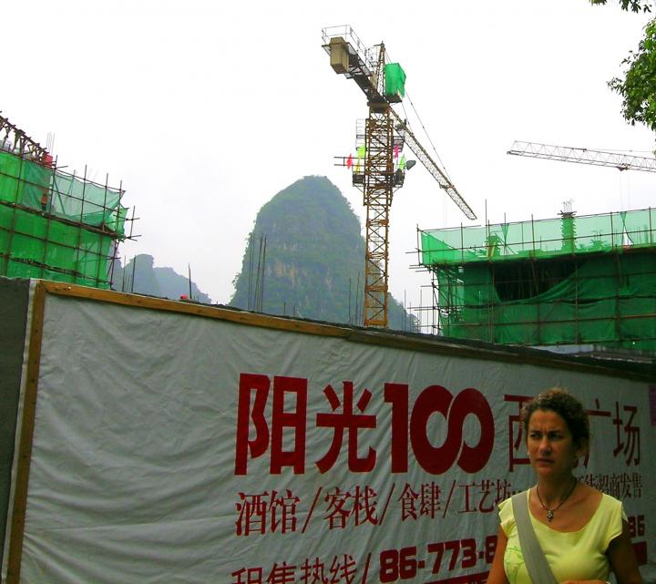 The cranes rise higher than the hills in Yangshuo