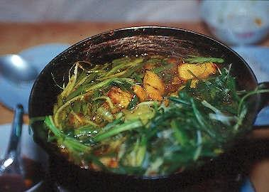 Braised fish sautéed with fresh herbs at the Cha Ca La Vong Restaurant, Hanoi, Vietnam.