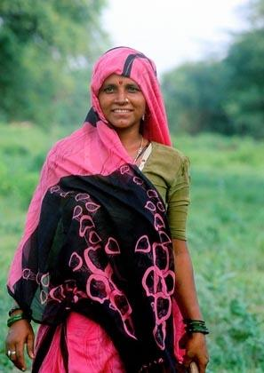 Bharatpur, Rajasthan, India: A colourfully sari-clad tribal lady cuts grass in Keoladeo Bird sanctuary.