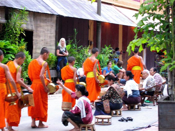 Monks are given rice by faithful women  on their early morning walk through Luang Prabang