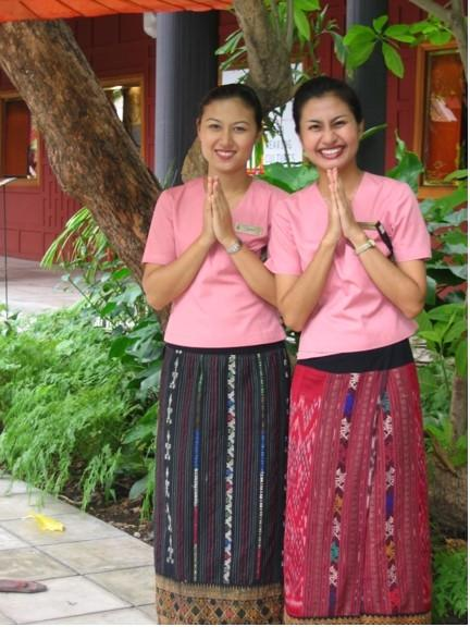 Smiling Thai guide welcome visitors to the Jim Thompson home in Bangkok