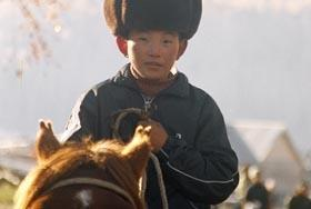 Fur-capped little man in Hemu village, Kenas. Xinjiang province, China.