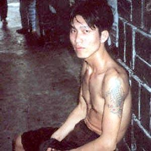 A young man with tattoos sits in the corner of a street in downtown Ho Chi Minh.