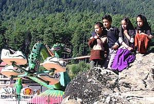 Two Kashmiri brothers and their twin sisters sit on a rock looking at rides inside Kashmir's first amusement park in Pahalgam.