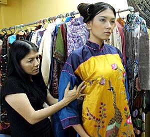 Designer Dang Thi Minh Hanh checks one of her creations with a model at her studio in Ho Chi Minh City, Vietnam.