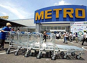 An employee pushes handcarts in front of the first Metro Cash and Carry wholesale center in Hanoi. Germany's Metro Group plans to open eight wholesale centers in Vietnam.