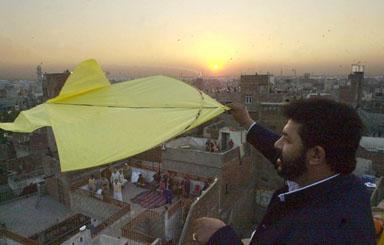 A man flies a kite at sunset after a day-long kite flying festival, locally known as 'Basant', in Pakistan's eastern city of Lahore, 09 February 2003, as officials said around 100,000 people from inside and outside the country had arrived in the city to celebrate the occasion. Two people died and more than 100 were injured during the annual kite flying festival marking the advent of spring in Pakistan. Public parks and rooftops were crowded with revellers celebrating the festival which started with music concerts and dinner parties organized privately or as public events late Saturday.