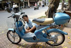 A mecanic puts the last finishing touch on a Chinese-made electric motorbike before its delivery in front of a bicycle shop in downtown Hanoi.
