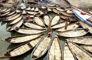 Boatmen make preparations on their vessels before setting out on the Buriganga river in Dhaka.