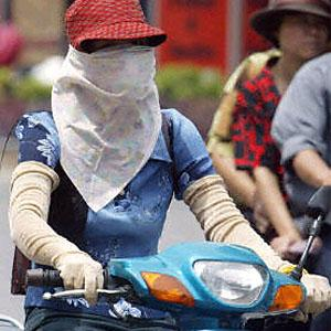 A masked woman wearing long gloves rides a motorcycle in Hanoi. Beauty in the minds of most Vietnamese women means white skin-a symbol of feminity, pureness, sophistication and high social class.