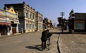 A man pushes his bicycle through a deserted film set at the Korean Feature Film Studio just outside the North Korean capital of Pyongyang.