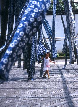 A young girl plays in the skeins of traditional blue and white tie-died fabric as they dry in a courtyard.