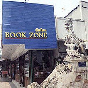 "Here is shown a modern bookstore crowding out a deteriorating ""singha"", or lion, at the entryway to a temple."