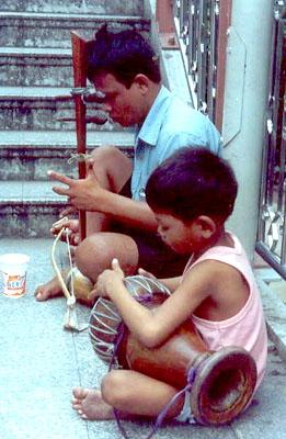 A boy beats on a drum while his father plays a Thai saw.