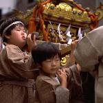 One of Japan's most honored traditions is the Omikoshi Matsuri, the annual Shinto festival. Nearly every Shinto shrine in Japan holds a mikoshi parade, in which a miniature replica of the shrine containing an image of the honored deity is transported through the surrounding streets on the shoulders of local patrons. Depicted here is a youthful version of a traditional mikoshi parade.