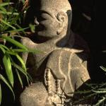 Nestled in a quiet corner of this tiny private garden, a stone Buddha adds an element of contemplative serenity.