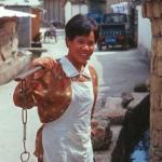 """Han Lady fetching water, in Lijiang """"new"""" town. Lijiang, Yunnan, China."""