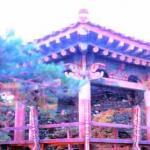 Sunrise gilds a pavilion of Naksansa Temple, near the seashore.