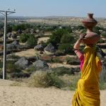 Ethnic Hindu woman carrying her matkas (water carriers) to her village below.