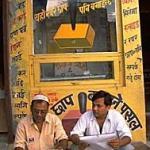 Two men reading newspapers by a stamp kiosk. Nepalganj, Nepal.