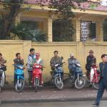 Motorcycle drivers wait for fares on a Hanoi street