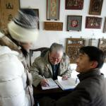 A young man and his girlfriend hover impatiently as an elderly man scribbles on a sheet of paper -- awaiting not a fortune, but a new name, at a licensed shop located near a Beijing Buddhist temple.<b