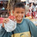 A young boy helps his mother sell souvenirs at an outdoor stand near Angkor Wat