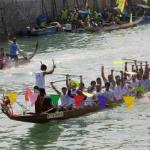 The Esso dragon boat crew lift their paddles in the air as they cross the finish line in the dragon boat races on Lamma Island, Hong Kong, 16 April 2001. The dragon boat races are an annual event and this year was won by a local crew under the banner of Esso.
