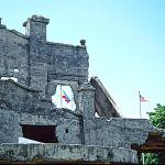 The flags of the Philippines and the United States fly above the ruins of the American military garrison.
