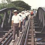 """Mange turister tager en tur over """"Broen over floden Kwai"""" til fods, før de sætter sig i toget for at lade sig transportere på en måde, der kan få nostalgien frem i enhver rigtig dreng ? ikke mindst de lidt større og ældre. 16.000 allierede krigsfanger mistede livet, da de blev tvunget til at anlægge jernbanen og bygge broen. Mindst 100.000 asiatiske tvangsarbejdere døde."""