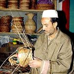 An Indian Kashmiri artesan makes a basket to contain a Kanger, a small clay pot suspended in a basket for carrying burning charcoal underneath overcoats during the winter months.