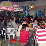 Foreign students gather at the Bla Bar at Beijing's Foreign Languages University on a typical Friday night 24 September 2004. With more than 30,000 foreign students living and studying in Beijing, a part of the capital's Haidian university district has turned into a cosmopolitan party center where students from around the world gather against a distinctly Chinese backdrop.