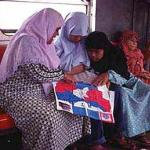 Muslim women poring over a map on a Jakarta train