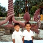 Two boys pose in front of the downtown Kratie fountain.