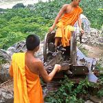 Novice monks play with a Russian anti-aircraft gun on top of Phou Si, above the old royal capital of Luang Prabang. Decades of war left many unwanted legacies, including unexploded ordnance.