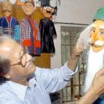 Bangladeshi artist Mostafa Monawar, known as the 'puppet man' puts the final touches to a puppet in Dhaka.