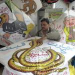 A shopkeeper gives the final touches to a kite decorated with a dragon and slogans to symbolise the Indian occupation in disputed Kashmir, on the eve of the annual kite-flying festival, locally known as 'Basant', in the eastern city of Lahore, 07 February 2003. This is first time that kite manufacturers have printed slogans about the current affairs of the world during the Basant festival. Basant is celebrated at the onset of each spring with an orgy of kite-flying, roof top soirees, garden parties and equestrian events.
