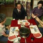 These guests are seated around a dinner table featuring one of Japan's many 'hot pot' dishes. Diners cook their own food in the simmering broth and remove it one bite at at time.