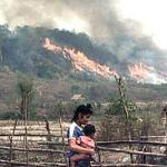 A young woman with a baby in the fields as vegetation is burnt off in the background, at a Hmong village resettled in the Xiengkhone district of the northern Laos province of Xayaburi.