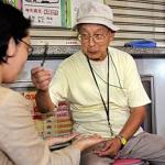 Seventy-eight-year-old fortune-teller Terutsugu Eguma attends to a customer on the street of Ginza shopping district of Tokyo.