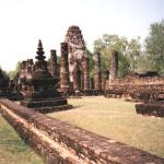 Part of an ancient building, with a statue of Buddha in the background. This buildings surround the entrace of an ancient Wat.