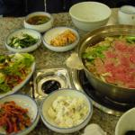 A meal of beef slices with dumplings boiled in a delicious broth cost KRW12,000 per person. Other side dishes include kimchi, preserved cabbage, potato salad, soup and more.