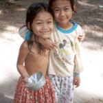 Two young girls stop to giggle at tourists in a Phnom Penh street.
