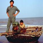 Two fishermen return to the beach in their lacquer boat.