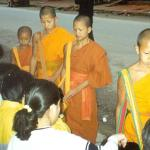 Young novice monks make their early morning alms rounds through the streets of Luang Prabang.