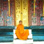 A monk rests on the steps of a pavilion at Wat Xiang Thong.