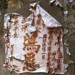 Tattered poster peels off a wall in Chinatown.