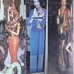 The wai appears commonly in Thai sculpture: far left in bronze, far right in wood. The life-like woman in the middle is a cardboard cut-out advertising Thai Airways.