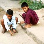 Two boys plan an intense game of marbles in a Phnom Penh street.