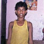 Varanasi, India. The gods, Siva among them, watch over this boy working in a restaurant in Varanasi.